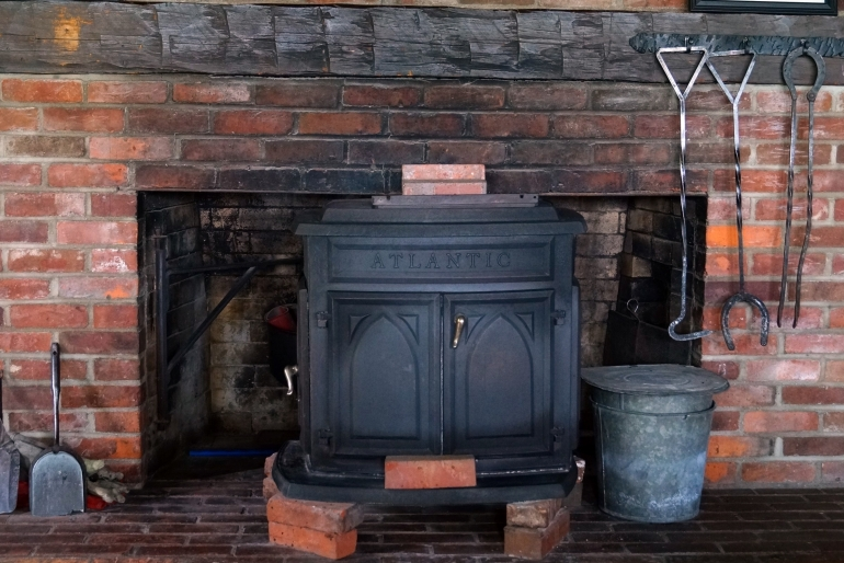 A Large Brick Fireplace Includes A Wood Stove