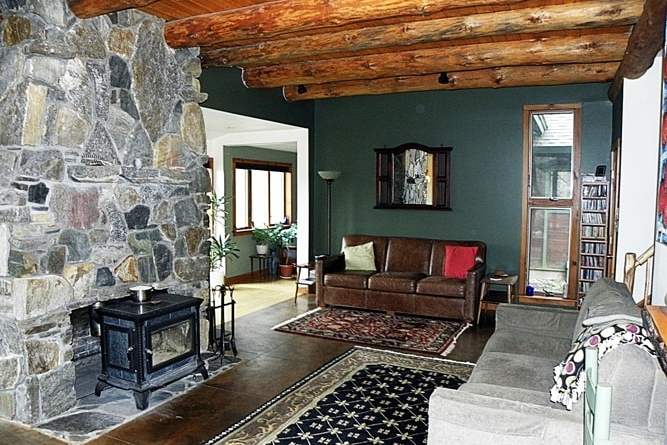 Great Room With Fireplace And Log Rafters